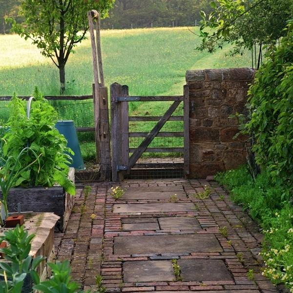 Большие плитки из известняка, уложенные поперек дорожки, обрамленные по краям клинкерными кирпичиками, создают ощущение, что путь к садовым воротам короче, чем на самом деле.
