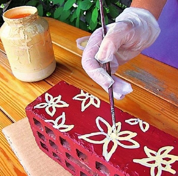 Когда краска высохнет, распишите торцы кирпичей симпатичными желтыми ромашками с асимметричными лепестками.