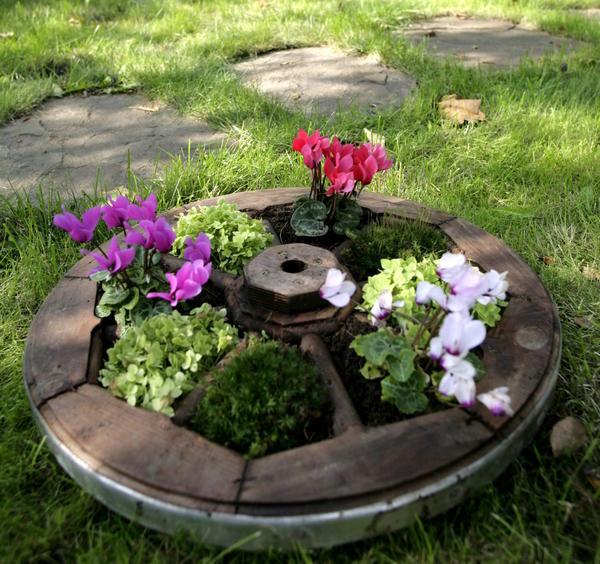 Если у вас есть старое или декоративное колесо от телеги, вы можете сделать похожую композицию, только из луковичных.