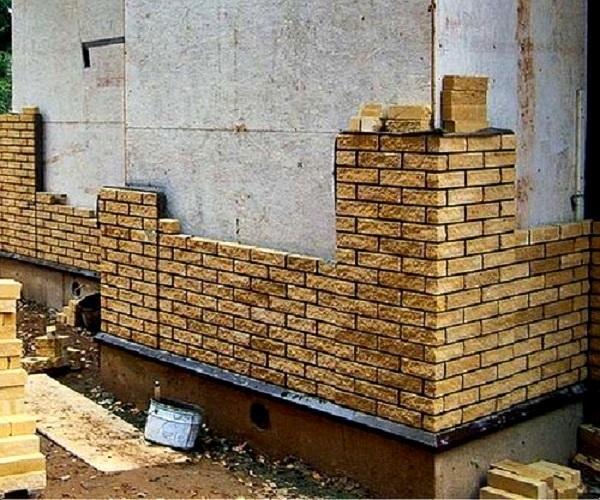 Возведение кирпичной облицовочной стены вдоль несущей каркасной стены. Фото: Бако