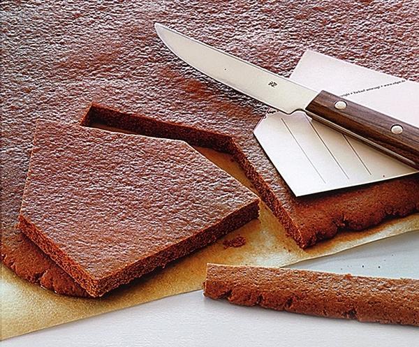 Сразу же выложите сверху шаблоны, пока тесто горячее, и вырезайте формы.