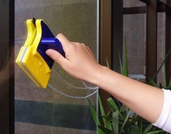 Мытье окна магнитной щеткой. Фото с сайта irecommend.ru.