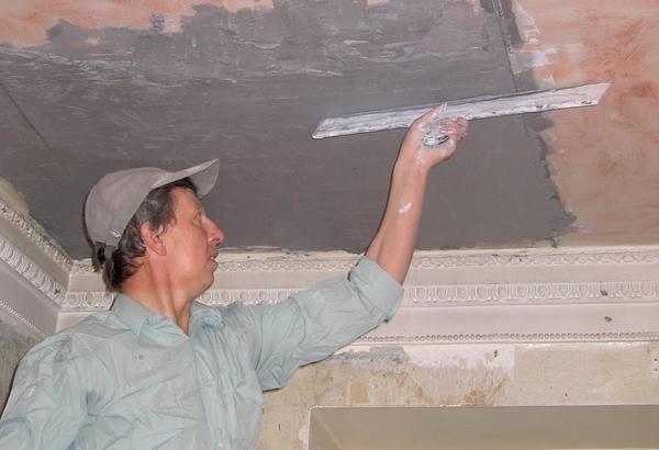 Выравнивание потолка по установленным маякам. Штукатурка представляет собой затворенную в воде ССС.