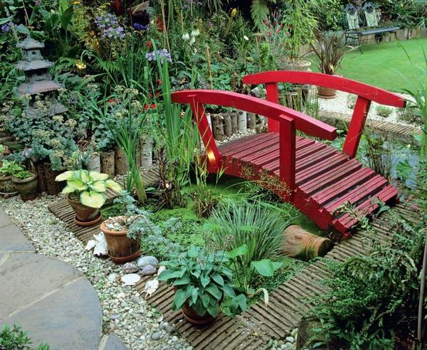 Декоративный рубеж - изогнутый мостик - ярким акцентом выделяется среди болотных трав