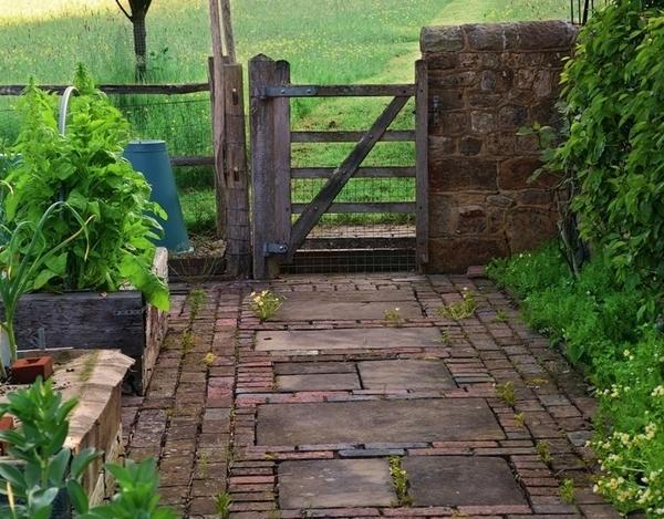 Большие плитки из известняка, уложенные поперек дорожки, обрамленные по краям клинкерными кирпичиками, создают ощущение, что путь к садовым воротам короче, чем на самом деле
