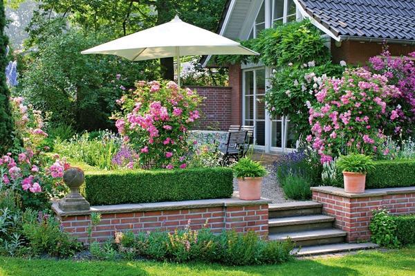 Низкая подпорная стенка удачно сглаживает перепад высот между террасой и садом. Каменные плиты, которыми накрыт верхний ряд кладки, защищает кирпичи от влаги