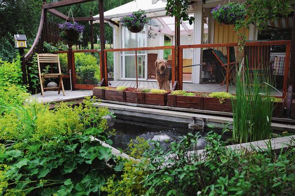 Растения в деревянных кашпо хороши везде: и на ступенях дома, и стоящие вдоль веранды, и на берегу водоема