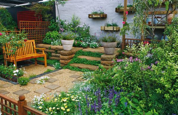 Перепад высот в саду можно обыграть, создав террасу из камня, на которой уютно разместятся вазоны с растениями и небольшие клумбы