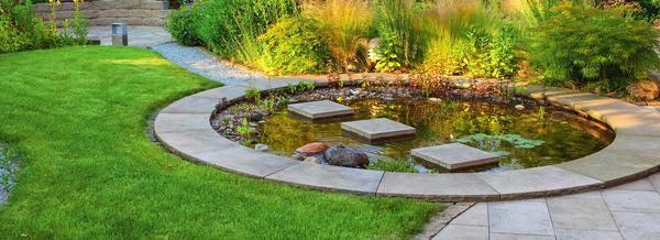 Квадратные шаговые плиты уложены посреди круглого водоема.Стоя на такой дорожке, можно наблюдать за жизнью в воде в непосредственной близи