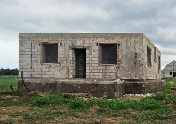 Такой недостроенный дом покупать нельзя. Бетон коричневый и по внешнему виду крайне непрочный. Пенобетонные блоки разрушились от воздействия влаги