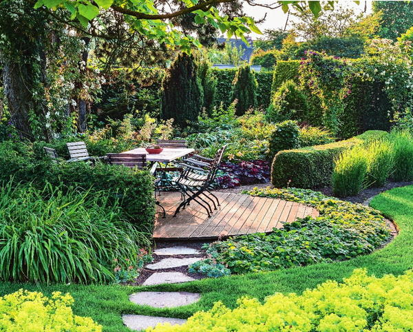 Круглую форму террасы поддерживают лилейники, живая изгородь из тиса и гравилат