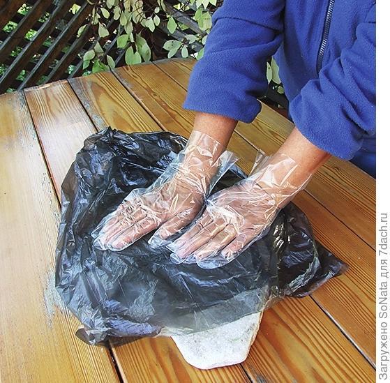 Накройте конструкцию полиэтиленом и плотно прижмите руками листья к камню.