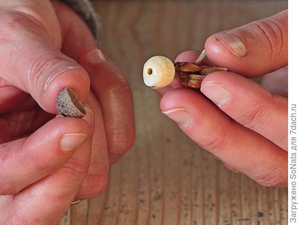 На верхнюю сторону деревянной бусины также капните немного клея и наденьте шапочку.