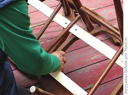 Приготовленные рейки располагаем параллельно, соединив оба стула, и закрепляем с помощью шурупов.