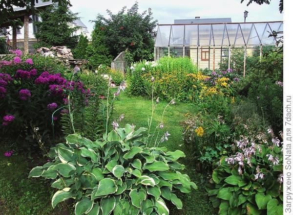 Теплица нисколько не испортит живописный садовый пейзаж, если для нее правильно выбраны место и компания.