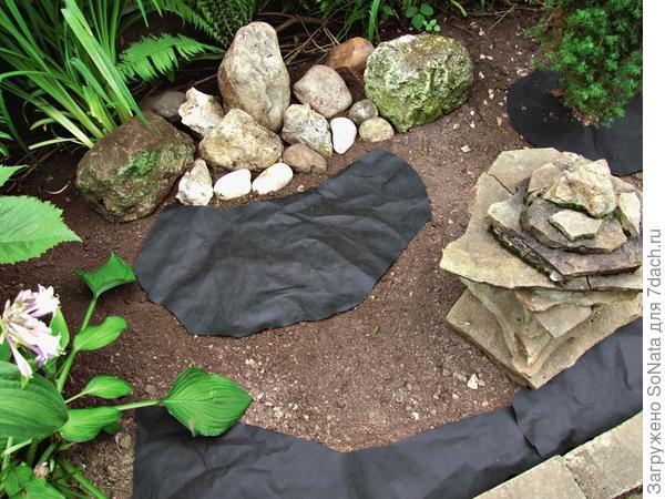 Разрежьте геотекстиль на куски подходящей формы и размера и застелите им все отмеченные островки.