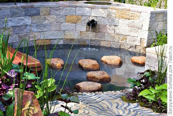 Полукруглая каменная стенка создает особый акцент на берегу пруда.