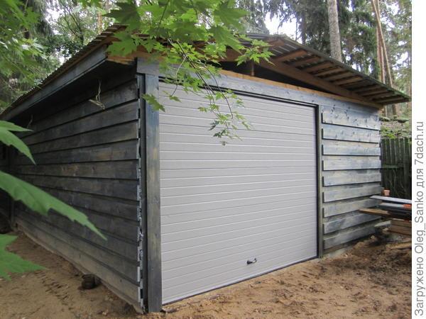 Цвет покраски гаража выбрали не броским, он не доминирует на лесном участке
