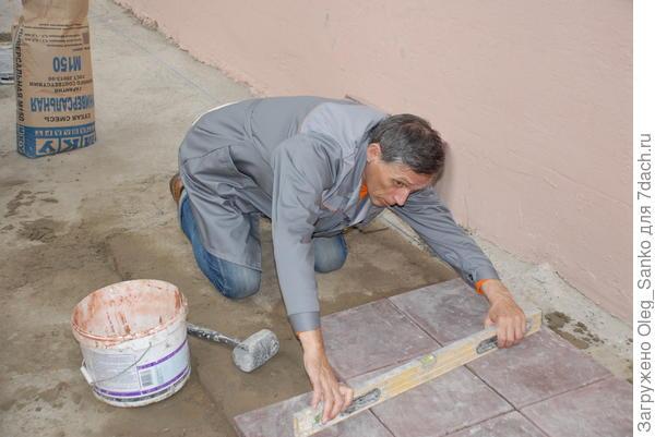 Автор статьи на работе по укладке тротуарных плит на универсальную сухую смесь