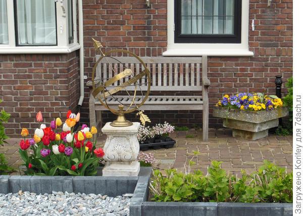 Обычная скамейка и напольная ваза с виолками, вот и все что надо для садового уюта