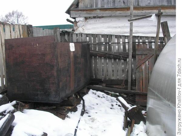 Двухкубовая емкость для сбора дождевой воды поднят на небольшой курган и на бревна.