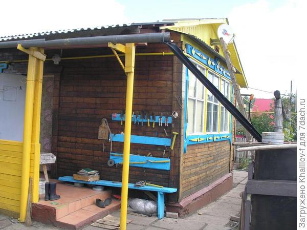 Желоб на западной стороне крыши у крыльца. А на стене синие доски, это у меня садовый инструментарий: на досках гвозди, а на них совки, секаторы прочее....