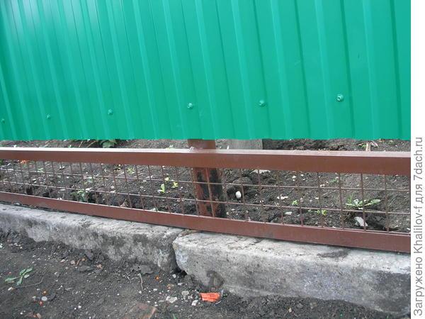 Сетка под забором из профнастила.