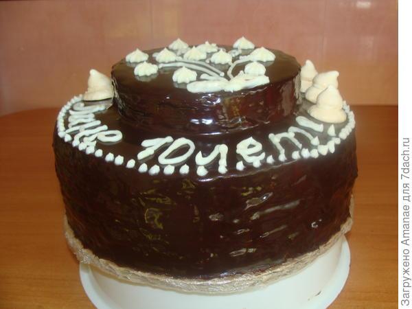 Двух ярусный торт с прослойками из безе и меренгами наверху.