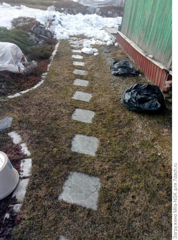 Вдоль дома уже снега нет, почва хоть и влажная, но не проваливается.