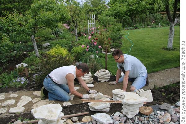 муж и сын укладывают камень