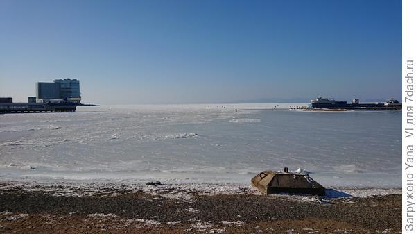 Вдали на льду сидят рыбаки...