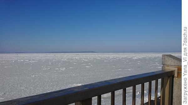 Другой берег залива в голубой дымке.
