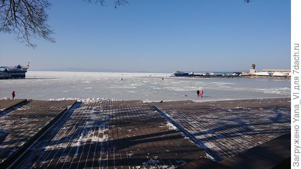 Летом здесь купаются. Вдали на льду сидят рыбаки...