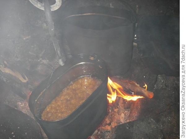 Варенье из свежесобранной морошки варится в котелке