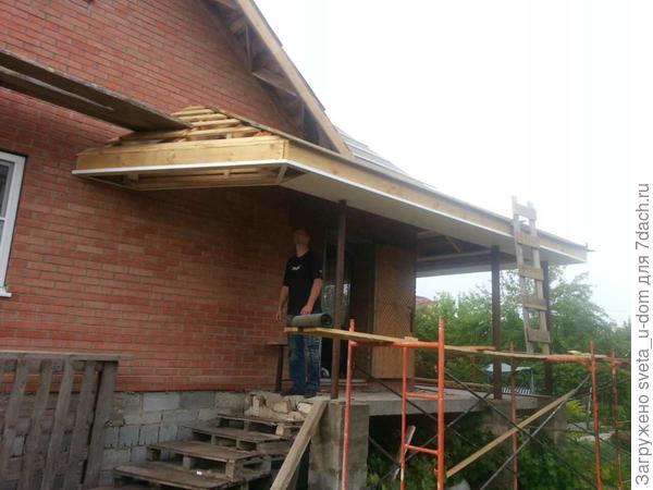Новый навес над главным входом, муж смотрит на проделанную работниками работу.