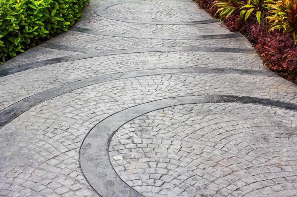 При создании дорожек можно смело миксовать бетон и брусчатку из натурального камня. И экспериментировать с узором