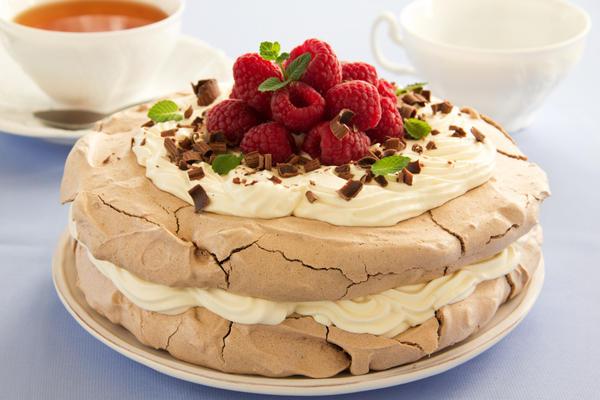 Торт «Павлова» из двух слоев меренги, украшенный малиной и шоколадной крошкой