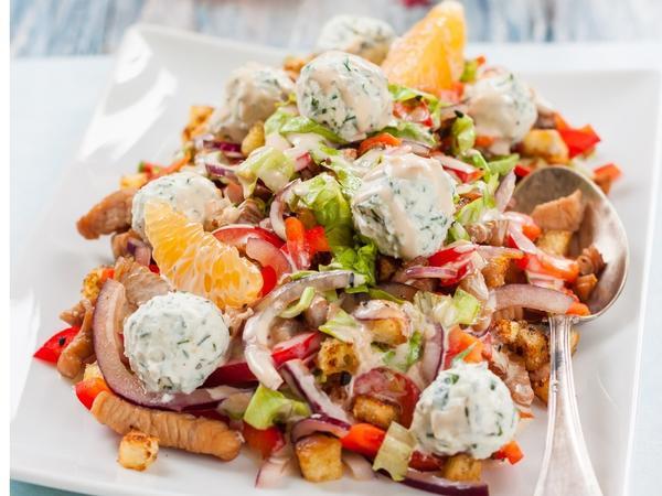 Нежный салат с курицей и апельсинами на тарелке