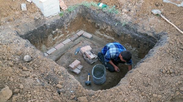 Небольшой котлован для отдельностоящего погреба. Мастер готовит основание для фундамента с помощью периметральной кирпичной кладки (для этих целей можно использовать доски). Фото с сайта svoimi-rykami.ru