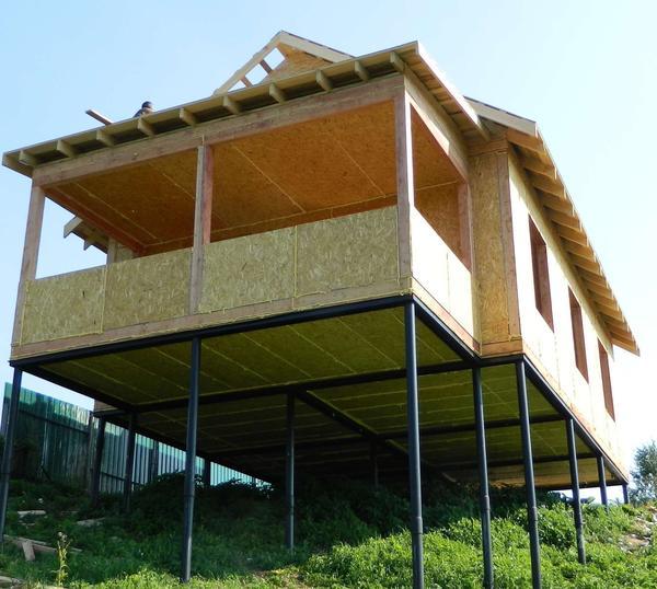 Фундамент из винтовых свай позволит построить дом даже на участке с крутым склоном. Фото с сайта полиол1.рф
