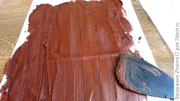 На пергаментный лист выкладываем тонким слоем в 1-2 мм растопленный шоколад