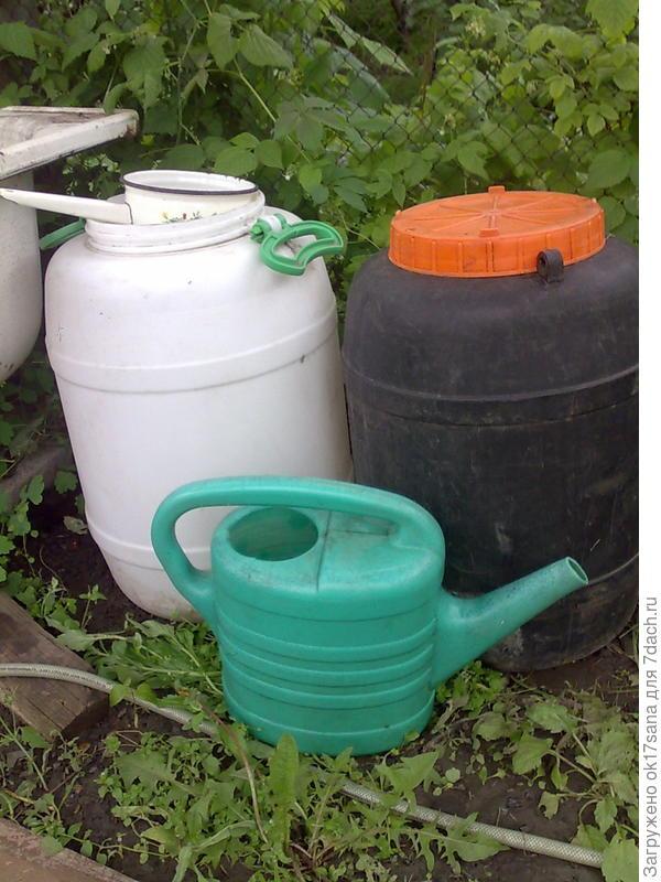 Две емкости с растворами для подкормки растений, лейка и ковш.