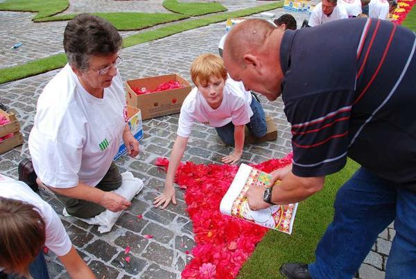 Работа волонтёров над созданием ковра из цветов. Фото с сайта flowercarpet.be