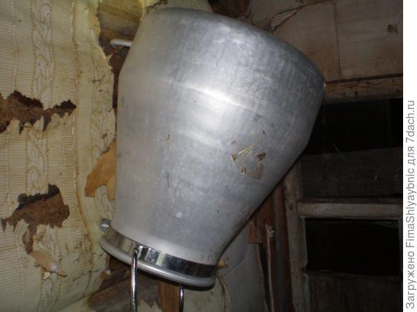 Доильное ведро висит в сарае на стенке