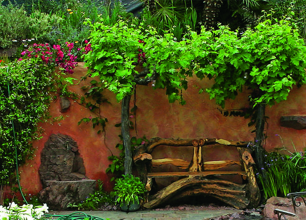 Ландшафтрая миниатюра в средиземноморском стиле: терракотовые стены, декоративный кран. Солистка - скамья из коряг.