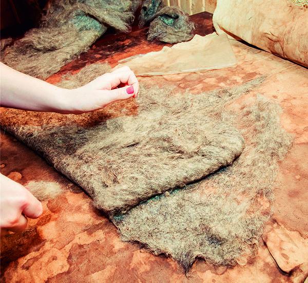Готовое шерстяное полотно женщины споро и ловко формируют в заготовки для валенок.