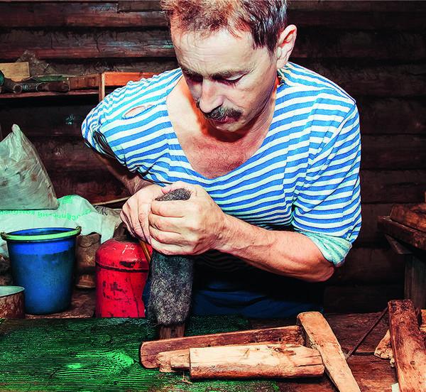 Чтобы придать изделию форму и размер ноги, валяльщик сажает его на соответствующую деревянную колодку