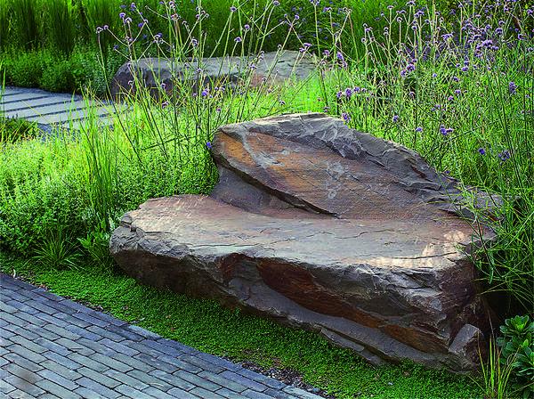 Из большой глыбы камня вручную вытесан вместительный диван со спинкой. Подобный арт-объект особенно гармонично смотрится в саду природного стиля.