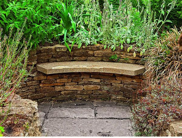 В полукруглую подпорную стенку встроена аккуратная плита, на которой можно расположиться на досуге. За сооружением растет теплолюбивый чистец византийский.