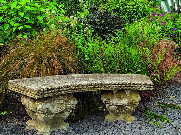 Изысканная скамья в классическом стиле эффектно отделяет цветник с декоративными травами от засыпанной серым сланцем дорожки.